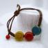 Pulsera para mujer de cerámica de colores  y con cordón marrón.