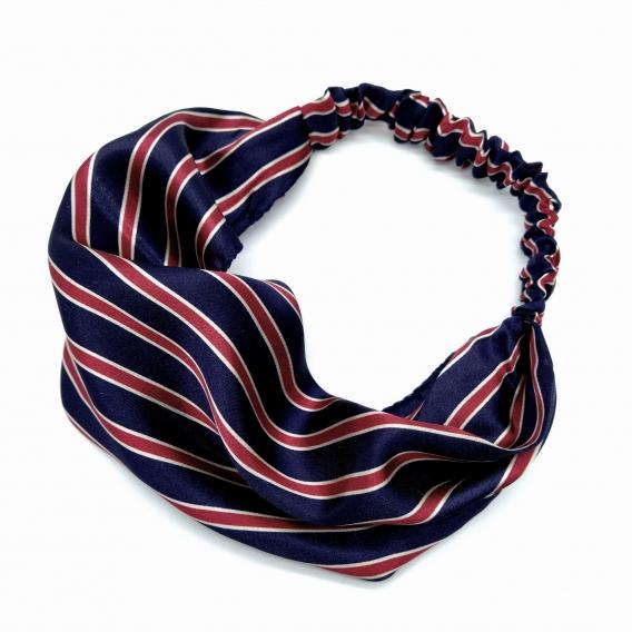 Diadema con forma de cinta elástica para el pelo de mujer, color a rallas azules, blancas y rojo oscuro.