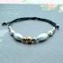 Pulsera con bolitas de acero y perlas de rio, en color oro, plata y rosa, con cordón negro y cierre ajustable